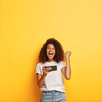 Excité jeune femme aux cheveux bouclés posant avec son téléphone