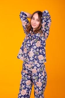 Excité jeune femme aux cheveux bouclés en pyjama à la maison, souriant largement en s'amusant. isolé sur