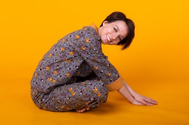 Excité jeune femme aux cheveux noirs en pyjama à la maison, souriant largement en s'amusant. isolé sur