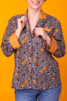 Excité jeune femme aux cheveux noirs en pyjama à la maison, souriant largement s'amuser