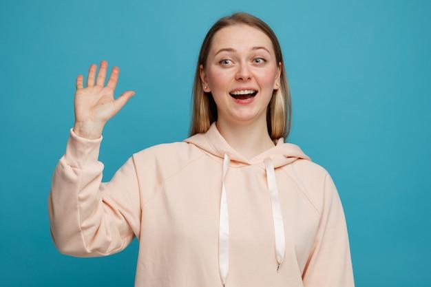 Excité jeune femme blonde regardant côté faisant le geste salut