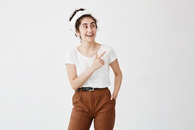 Excité jeune femme brune avec un nœud de cheveux pointant son index sur le côté, levant les sourcils et gardant la bouche grande ouverte, montrant quelque chose de surprenant sur le mur de l'espace de copie blanc
