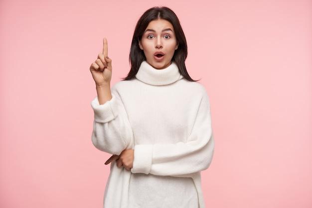 Excité jeune femme brune séduisante vêtue d'un pull en laine blanche gardant son index soulevé tout en regardant étourdi à l'avant, debout sur un mur rose