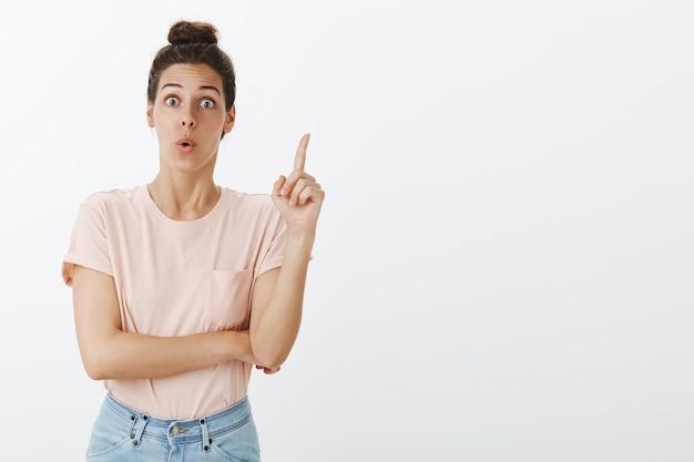 Excité jeune femme élégante posant contre le mur blanc