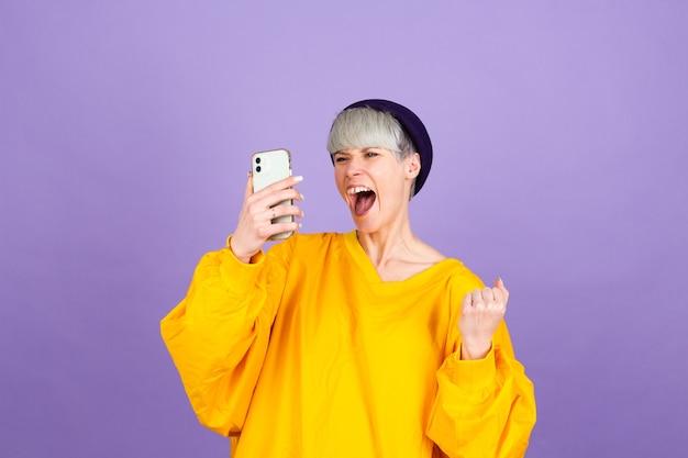 Excité jeune femme émerveillée par l'incroyable message de vente d'application mobile shopping à la recherche de smartphone, fille gagnant tenant un téléphone portable hurlant de joie