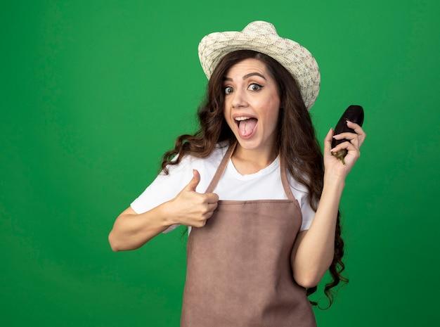 Excité jeune femme jardinière en uniforme portant chapeau de jardinage thumbs up et détient l'aubergine isolé sur mur vert avec copie espace
