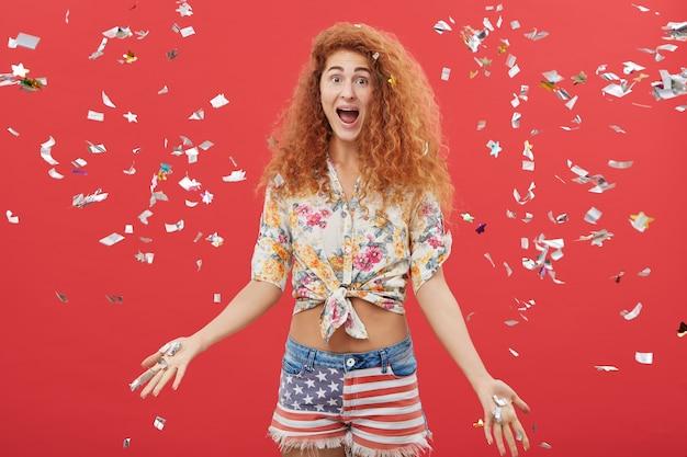 Excité jeune femme jetant des papiers en l'air en se tenant debout sur fond de studio rouge