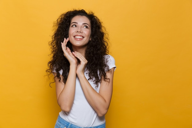 Excité jeune femme mignonne posant isolé sur jaune.