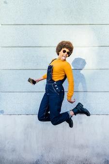 Excité de jeune femme noire sautant avec un smartphone.