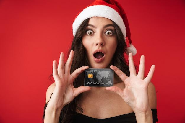 Excité jeune femme portant un chapeau de noël isolé sur rouge, montrant une carte de crédit en plastique