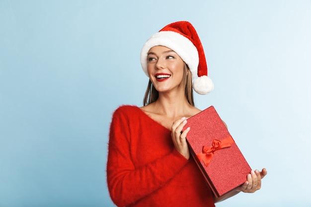 Excité jeune femme portant un chapeau de père noël rouge debout avec une boîte cadeau ouverte