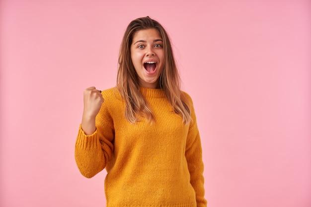 Excité jeune femme portant ses cheveux bruns en coiffure décontractée tout en posant sur rose avec la main levée avec la bouche grande ouverte