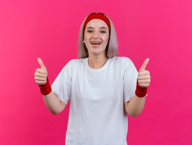 Excité jeune femme sportive avec des accolades portant bandeau et bracelets pouces vers le haut de deux mains isolé sur mur rose