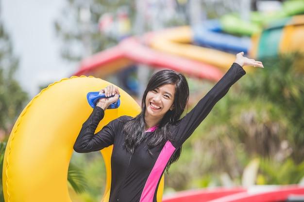 Excité de jeune femme avec un tube gonflable dans une piscine