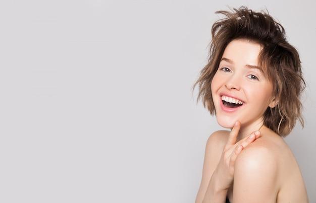 Excité de jeune fille souriante avec une peau et des dents parfaites présentant votre produit sur un mur gris isolé. beauté naturelle sans maquillage femme étonnée. espace libre pour le texte. expressions faciales expressives
