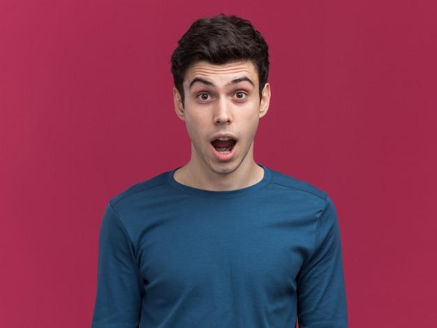 Excité jeune garçon caucasien brune regardant la caméra sur rose