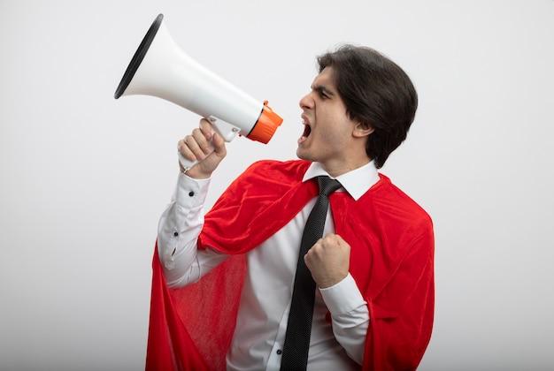 Excité jeune gars de super-héros regardant le côté portant une cravate parle sur haut-parleur