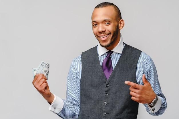 Excité jeune homme afro-américain tenant de l'argent comptant et pointant vers elle sur mur gris clair