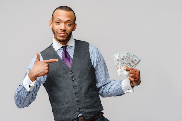 Excité jeune homme afro-américain tenant de l'argent comptant et pointe vers elle sur un mur gris clair