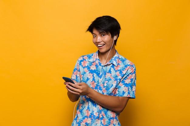 Excité jeune homme asiatique debout isolé sur un espace jaune à l'aide de musique d'écoute de téléphone mobile avec des écouteurs.