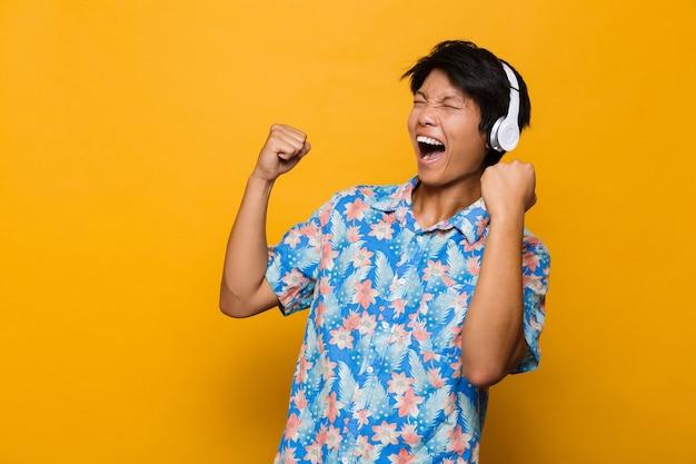 Excité jeune homme asiatique debout isolé sur un espace jaune, écouter de la musique avec des écouteurs faire le geste gagnant.
