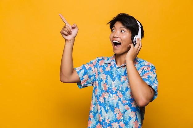 Excité jeune homme asiatique debout isolé sur un espace jaune, écouter de la musique avec des écouteurs pointant.