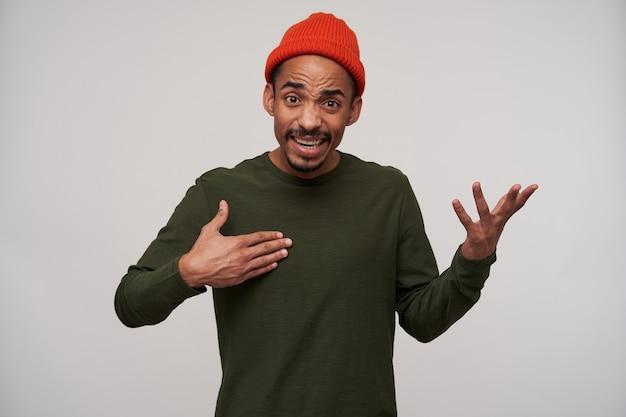 Excité jeune homme barbu aux cheveux noirs avec une peau foncée soulevant des paumes avec un visage confus, portant un chapeau rouge et un pull kaki tout en posant sur blanc