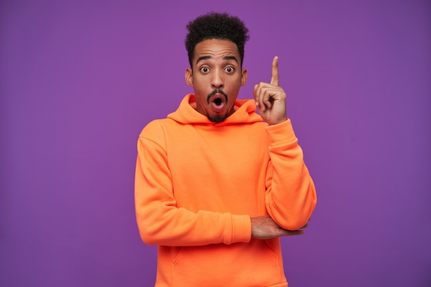 Excité jeune homme brune à la peau foncée barbu bouclé levant la main avec le signe de l'idée et soulevant les sourcils avec surprise, debout sur le violet dans des vêtements décontractés sportifs