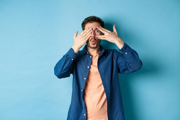 Excité jeune homme furtivement entre les doigts et disant wow, vérifiant le cadeau surprise, debout sur fond bleu.