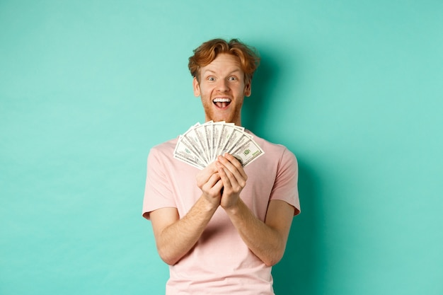 Excité jeune homme gagnant des prix en argent, comptant de l'argent et à la surprise de dollars, debout sur fond turquoise.