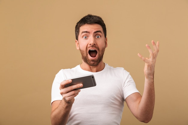 Excité jeune homme occasionnel jouant à des jeux sur téléphone mobile isolé