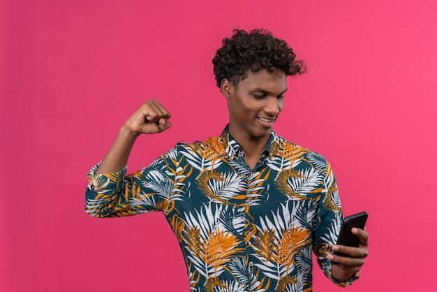 Excité jeune homme à la peau sombre avec des cheveux bouclés en chemise imprimée de feuilles en regardant son smartphone avec le poing serré