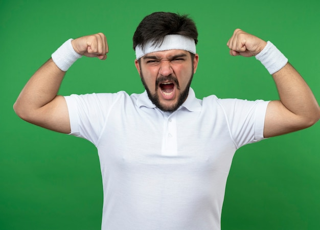 Excité jeune homme sportif portant bandeau et bracelet montrant un geste fort isolé sur vert