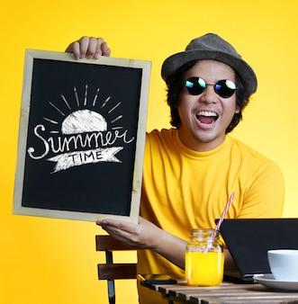 Excité de jeune homme tenant la typographie de l'heure d'été sur tableau noir tout en travaillant sur l'été