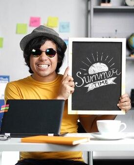 Excité jeune homme tenant la typographie de l'heure d'été sur tableau noir tout en travaillant