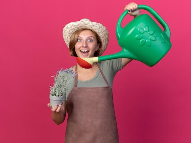Excité jeune jardinier femme slave portant chapeau de jardinage tenant un arrosoir et des fleurs en pot de fleurs sur rose