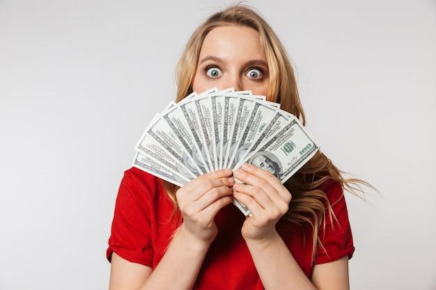 Excité jeune jolie belle femme posant isolé sur mur blanc mur tenant de l'argent