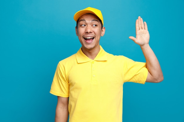 Excité jeune livreur portant l'uniforme et une casquette regardant le côté faisant le geste salut