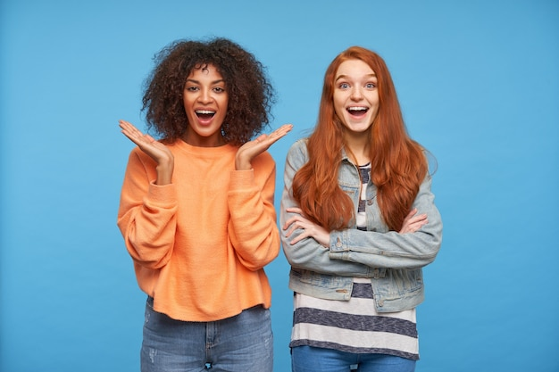 Excité de jeunes belles copines regardant joyeusement et gardant la bouche grande ouverte, étonné de quelque chose tout en posant sur le mur bleu