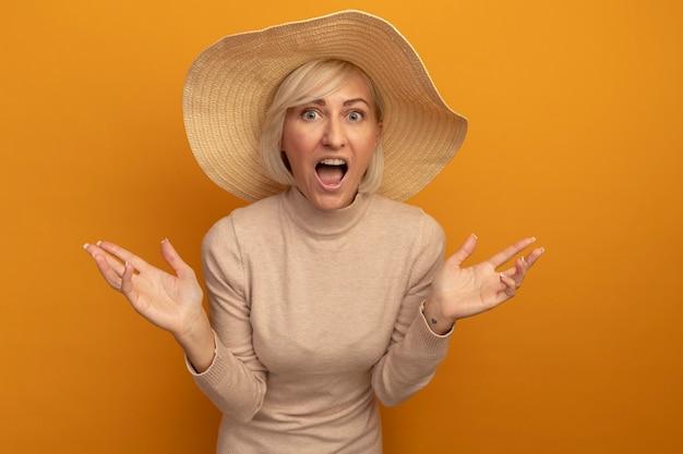 Excité jolie blonde femme slave avec chapeau de plage tient les mains ouvertes et semble isolé