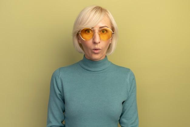 Excité jolie blonde femme slave dans des lunettes de soleil semble isolé