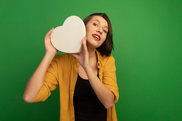 Excité jolie femme caucasienne tenant en forme de coeur sur vert