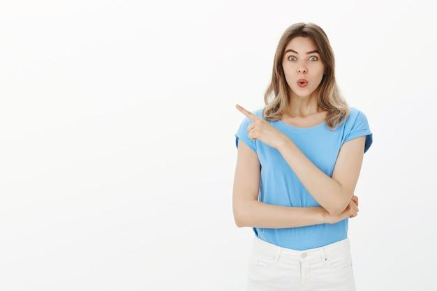 Excité jolie femme pointant le doigt à gauche sur des nouvelles incroyables, montrant la publicité