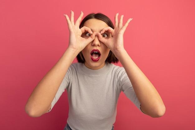 Excité jolie femme regarde à travers les doigts isolés sur mur rose