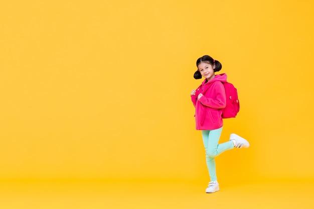 Excité jolie fille aux cheveux en queue de cochon aller à l'école