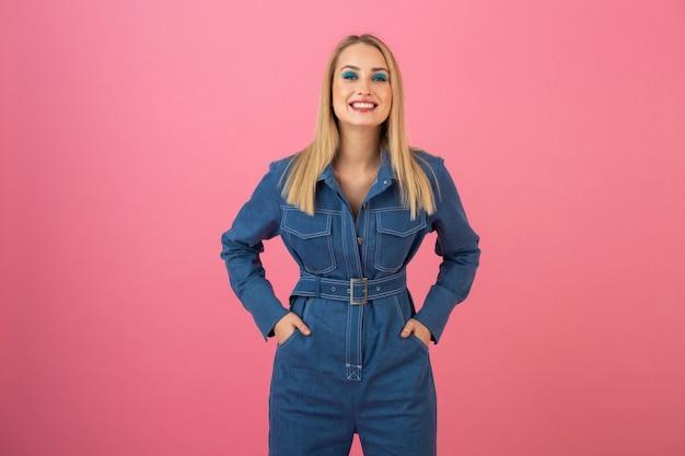 Excité jolie fille posant sur fond rose dans la tendance de la mode globale denim