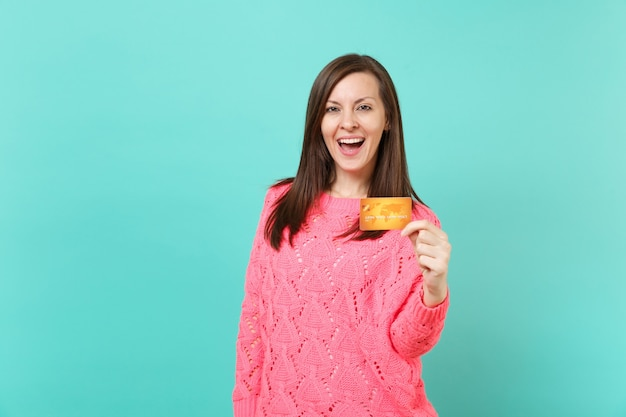 Excité joyeuse belle jeune femme en pull rose tricoté tenant à la main une carte de crédit isolée sur fond de mur bleu turquoise, portrait en studio. concept de mode de vie des gens. maquette de l'espace de copie.