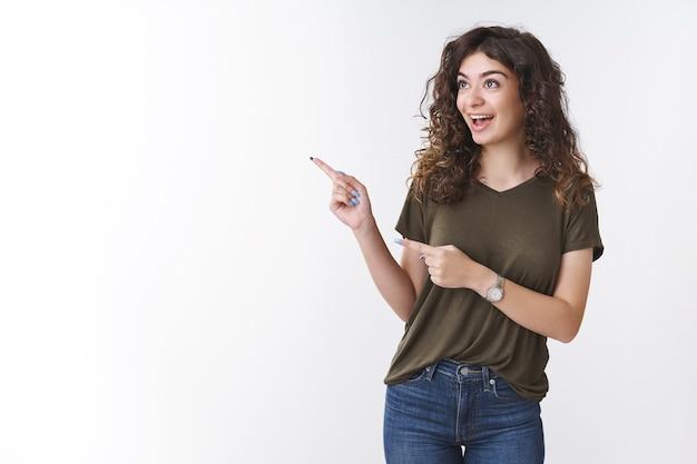 Excité joyeuse fille caucasienne aux cheveux bouclés sortante portant un t-shirt olive souriant amusée pointant du doigt à la fascination du coin gauche debout ravie intéressée veux acheter une superbe robe pour le bal