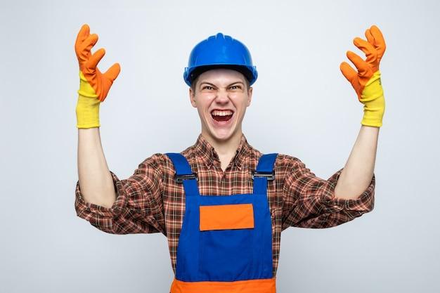 Excité levant les mains jeune constructeur masculin en uniforme avec des gants