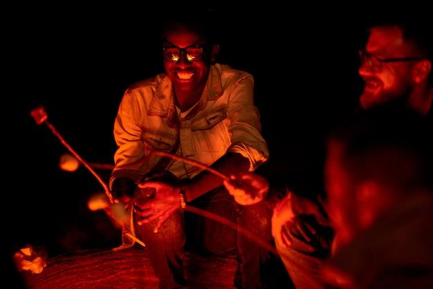 Excité mec africain cuisine guimauve sur feu de camp avec des amis